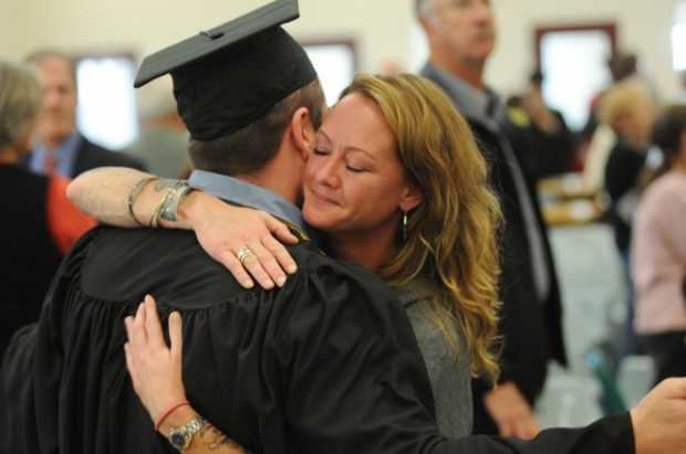 Inmate Steven Clark gets a hug from his girl friend Tomi Doyle after Clark received his associate degree from the University of Maine in Augusta on Monday at the Maine State Prison.